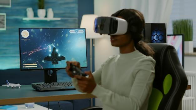 Jogador africano que joga a competição de atiradores espaciais usando óculos de realidade virtual. jogador competitivo usando joystick para campeonato online sentado na cadeira de jogo tarde da noite na sala de estar