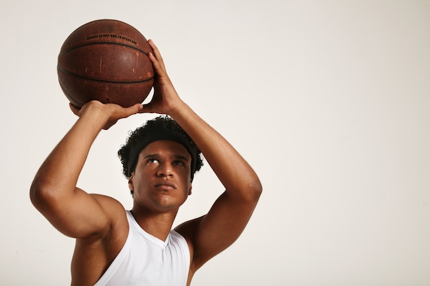 Jogador afro-americano focado em forma física com um afro curto em uma camisa branca sem mangas se preparando para lançar uma velha bola de basquete de couro