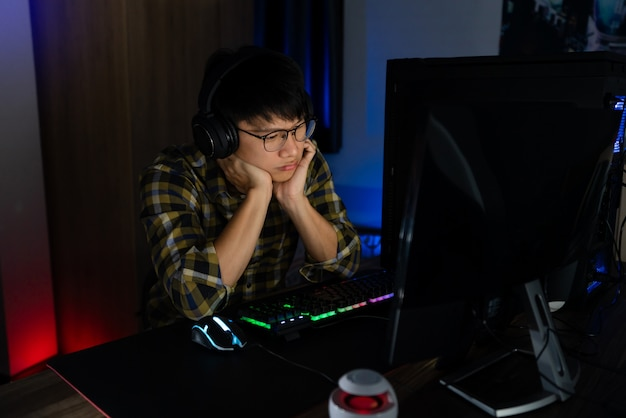Jogador asiático jogando em seu computador no meio da noite