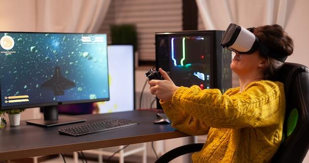 Jogador cibernético profissional relaxando jogando videogame usando fone de ouvido vr, jogo de tiro virtual tarde da noite ...