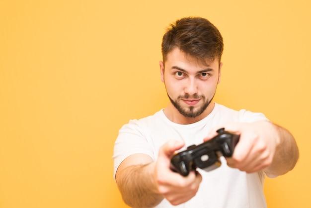 Jogador com barba jogando videogame no console, segura um gamepad nas mãos