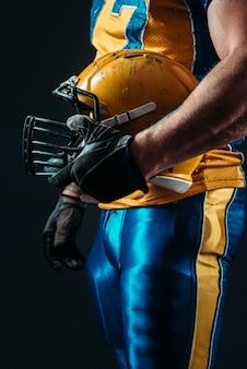 Jogador com capacete de futebol americano na mão