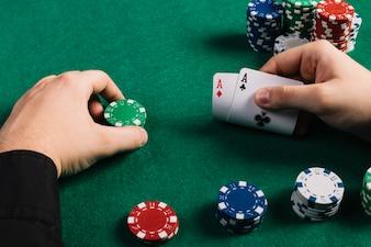Jogador com dois ases e fichas jogando poker