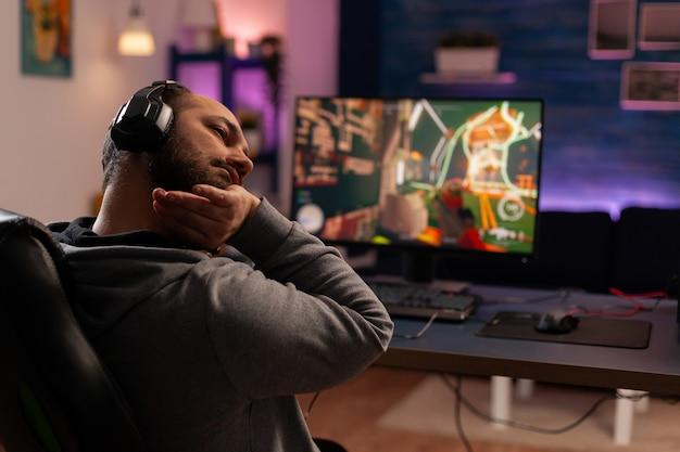 Jogador competitivo se espreguiçando na cadeira de jogos na mesa e jogando videogames de tiro na sala de estar. transmissão cibernética online durante o torneio de jogo usando um pc poderoso com rgb