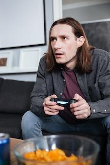 Jogador concentrado do homem que senta-se em casa dentro de casa
