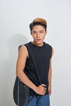 Jogador de badminton asiático com bolsa em fundo branco