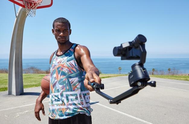 Jogador de basquete à beira-mar com câmera selfie