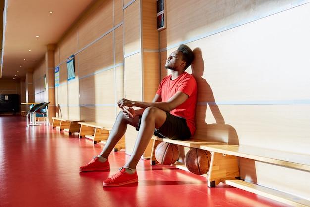 Jogador de basquete afro-americano cansado, sentado à margem