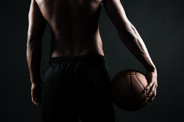 Jogador de basquete afro-americano, segurando uma bola