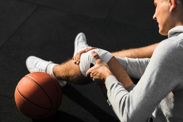 Jogador de basquete, aplicar curativo no joelho