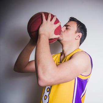 Jogador de basquete beijando bola