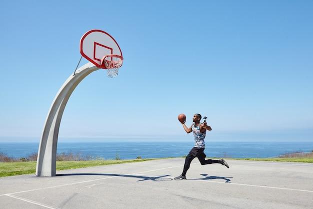 Jogador de basquete correndo à beira-mar com câmera selfie