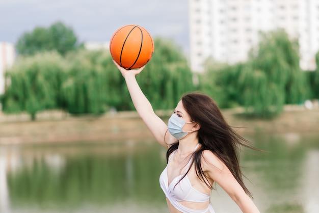 Jogador de basquete de mulher fitness jovem esporte usando máscara cobiçosa para proteger com bola, fundo do lago.