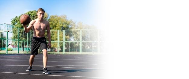Jogador de basquete de rua com bola no campo de esportes. banner com espaço de cópia
