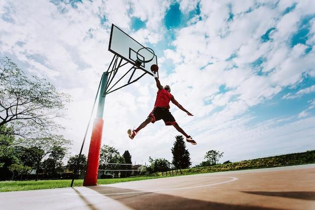 Jogador de basquete de rua dando uma enterrada poderosa na quadra