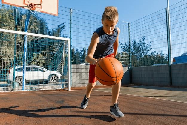 Jogador de basquete de rua de menino adolescente caucasiano com bola