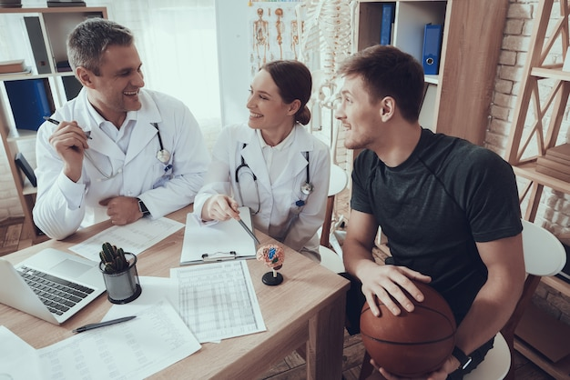 Jogador de basquete está sentado na clínica.