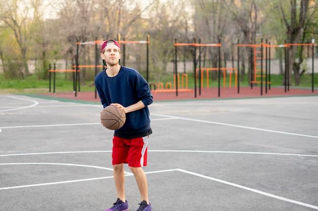 Jogador de basquete, fazendo exercícios de tiro ao ar livre nas quadras de rua da cidade