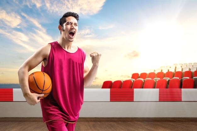 Jogador de basquete homem asiático, segurando a bola com uma expressão animada