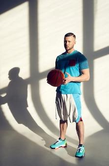 Jogador de basquete jovem atlético segurando uma bola e em pé perto da parede com sombras na janela