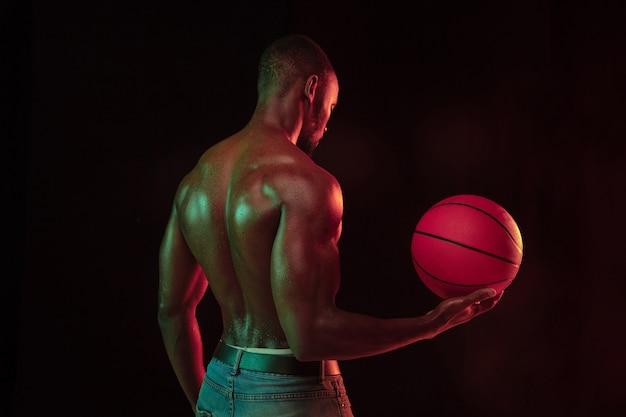 Jogador de basquete jovem musculoso afro-americano em ação de treinamento de jogabilidade, praticando em luzes de néon sobre o fundo escuro do estúdio. conceito de esporte, movimento, energia, estilo de vida dinâmico e saudável.