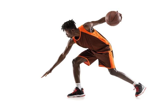 Jogador de basquete masculino afro-americano em movimento e ação isolado no branco