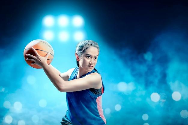 Jogador de basquete menina asiática animado defendendo a bola do adversário na quadra de basquete