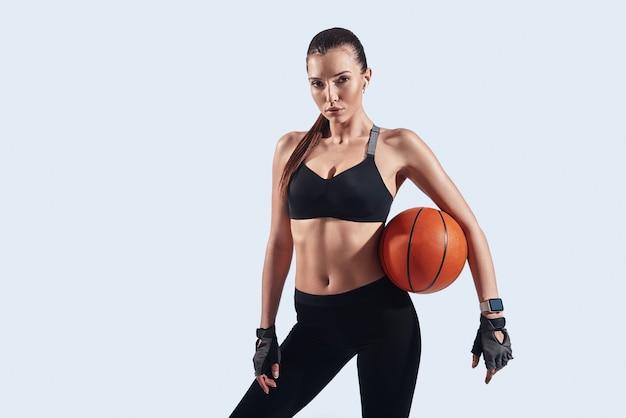 Jogador de basquete. mulher jovem e atraente olhando para a câmera em pé contra um fundo cinza