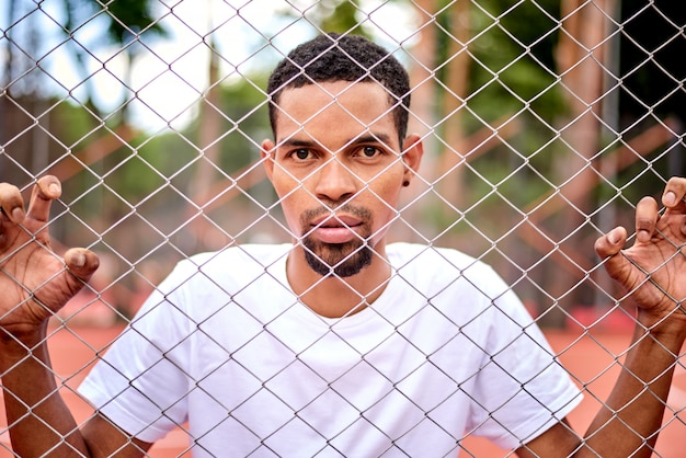Jogador de basquete negro segurando a cerca de arame com as mãos