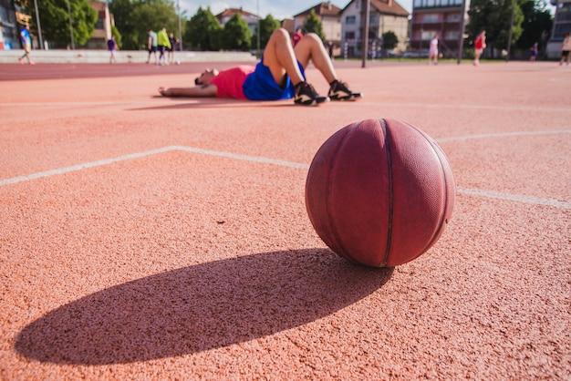 Jogador de basquete no chão com bola em primeiro plano