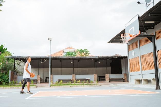 Jogador de basquete prestes a arremessar a bola para o aro