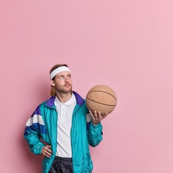 Jogador de basquete profissional atencioso no activewear segura a bola concentrada acima para jogar o jogo favorito.