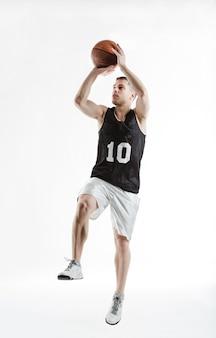 Jogador de basquete profissional que salta com a bola em suas mãos