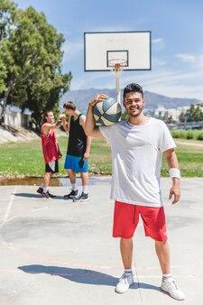 Jogador de basquete sorridente segurando a bola por cima do ombro