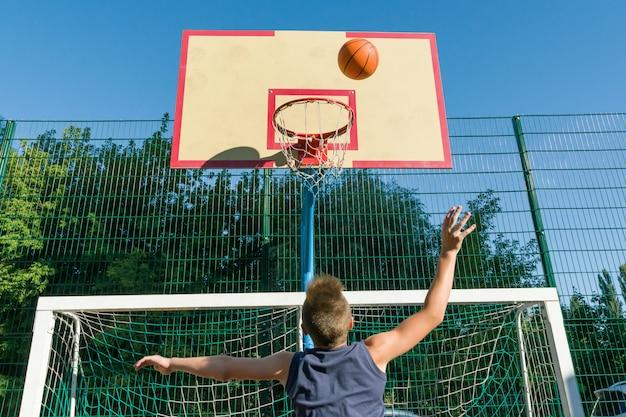 Jogador de basquetebol da rua do menino do adolescente no campo de básquete da cidade.