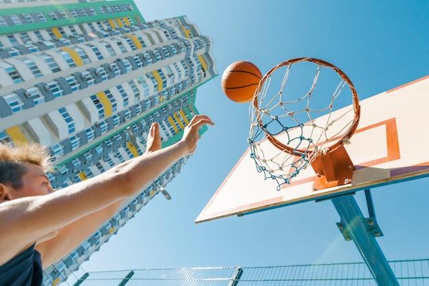 Jogador de basquetebol exterior da rua do retrato que joga com a bola no dia ensolarado.