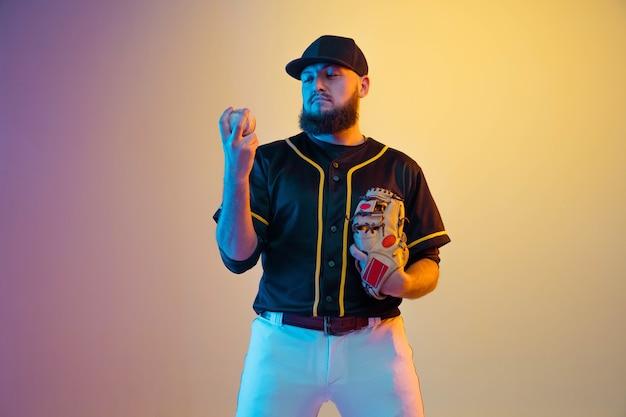 Jogador de beisebol, arremessador de uniforme preto, praticando e treinando na parede gradiente em luz de néon. jovem desportista profissional em ação e movimento. estilo de vida saudável, esporte, conceito de movimento.