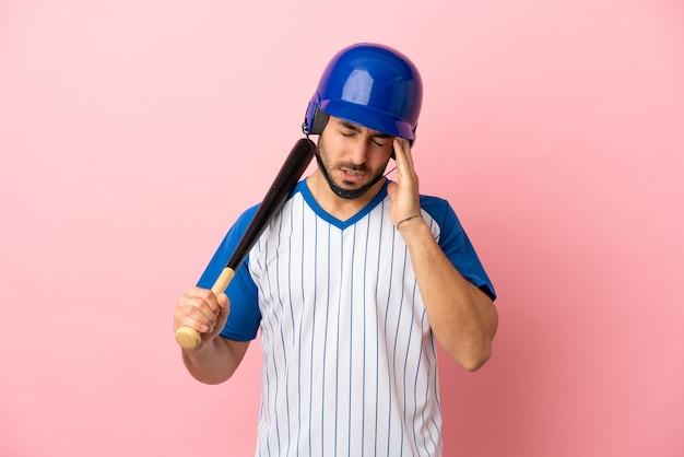Jogador de beisebol com capacete e taco isolado em fundo rosa com dor de cabeça