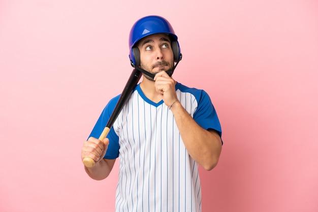 Jogador de beisebol com capacete e taco isolado no fundo rosa tendo dúvidas e pensando