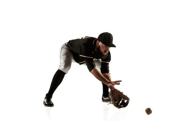 Jogador de beisebol, lançador de uniforme preto, praticando e treinando isolado em uma parede branca. jovem desportista profissional em ação e movimento. estilo de vida saudável, esporte, conceito de movimento.