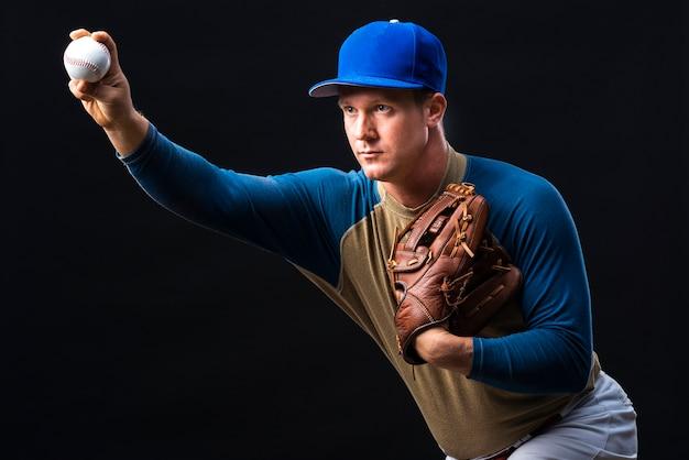 Jogador de beisebol posando com luva e bola