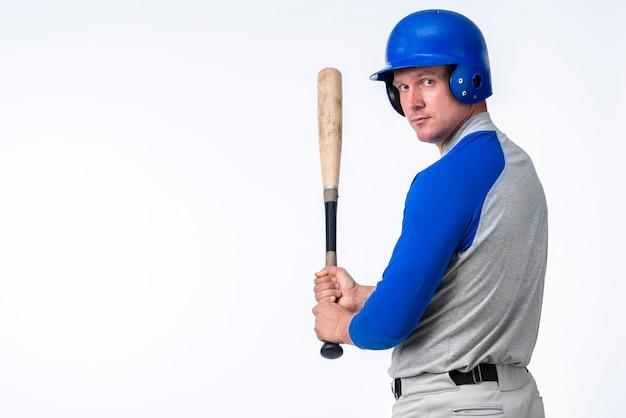 Jogador de beisebol posando enquanto segura o bastão