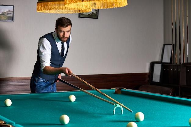 Jogador de bilhar encontrando a melhor solução e ângulo certo no jogo de bilhar ou sinuca, ele está concentrado