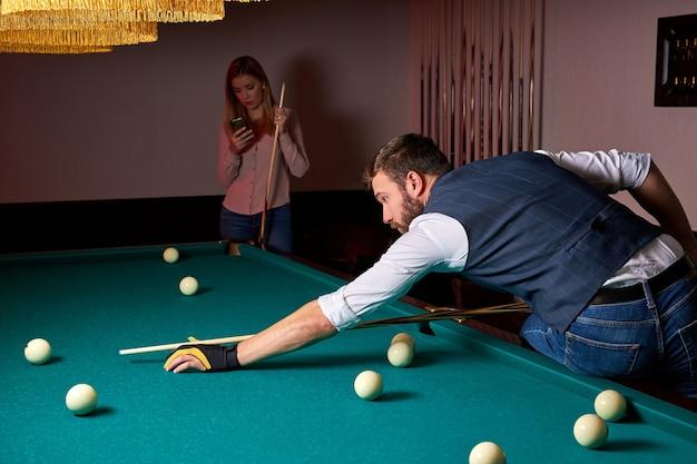Jogador de bilhar masculino encontrando a melhor solução e ângulo reto no jogo de bilhar ou sinuca, jogador profissional de bilhar está concentrado