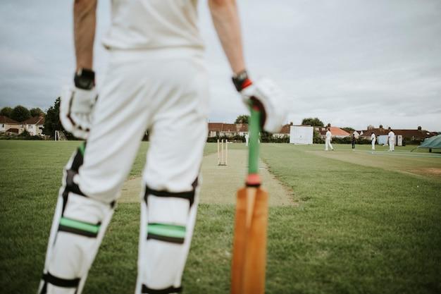 Jogador de críquete em pé em um campo