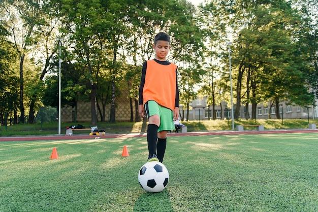 Jogador de futebol adolescente diligente enche a bola de futebol nos pés com botas. praticar exercícios esportivos em