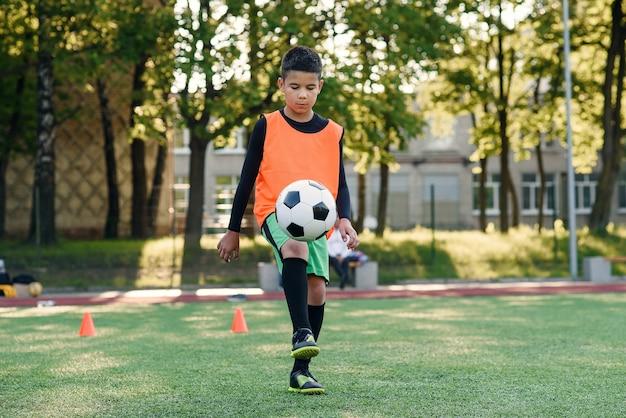Jogador de futebol adolescente diligente enfia bola nos pés com botas