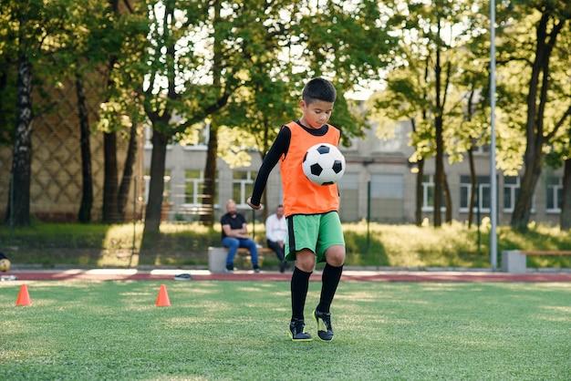 Jogador de futebol adolescente habilidoso concentrado enche a bola de futebol na perna.