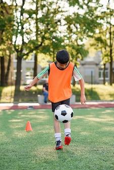 Jogador de futebol adolescente motivado enche a bola de futebol na perna. praticar exercícios esportivos em artificial