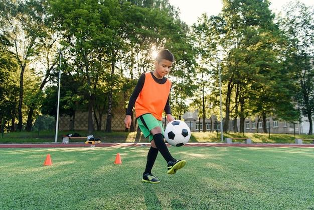Jogador de futebol adolescente motivado enfia bola nos pés com botas